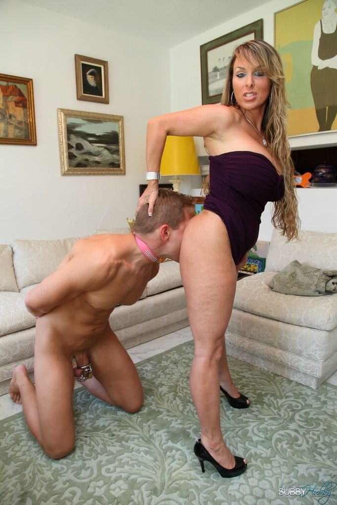 Buxom blonde mistress Holly Halston makes collared male slave lick vagina