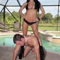 Cruel domme in high heeled boots Adrianna Lynn leading male slave on leash
