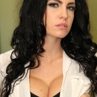 Enticing black-haired girl Emmanuelle London discards her miniskirt to unveil her clean-shaved muff
