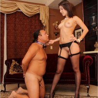 Missy Daniels in high heels and stockings leading her submissive husband by his collar