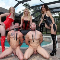 3 Dommes in fetish apparel manhandle two collared male slaves on the poolside patio