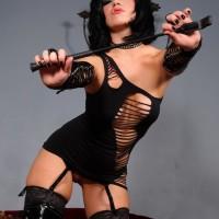 Authoritative type Belle Noir rocks a revealing black dress in thigh high boots