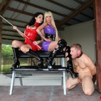 Latex attired females from Club Dom torture a male slave during electro play