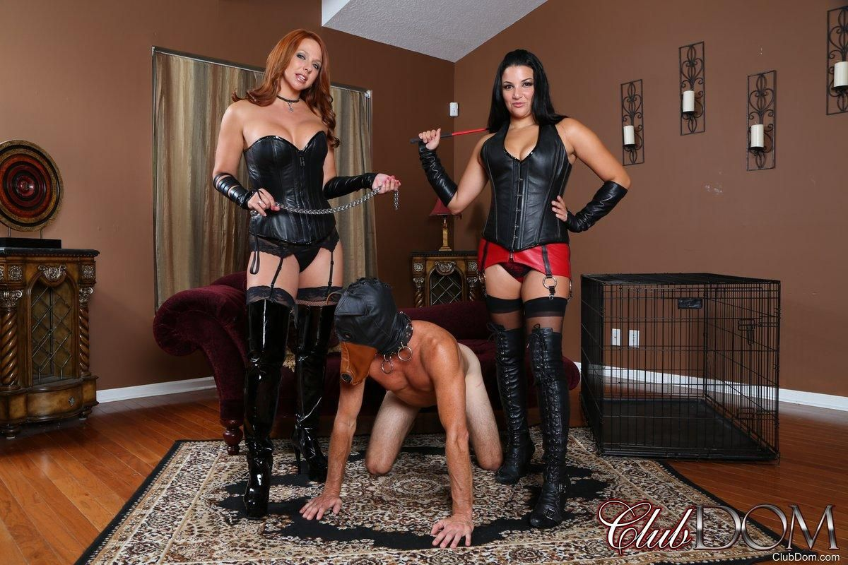 Fetish wear attired women lead sub male by leash with collar on before caging him