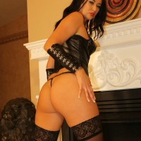 Hot brunette Mistress Ashley pinches her nipples in a leather corset and stockings