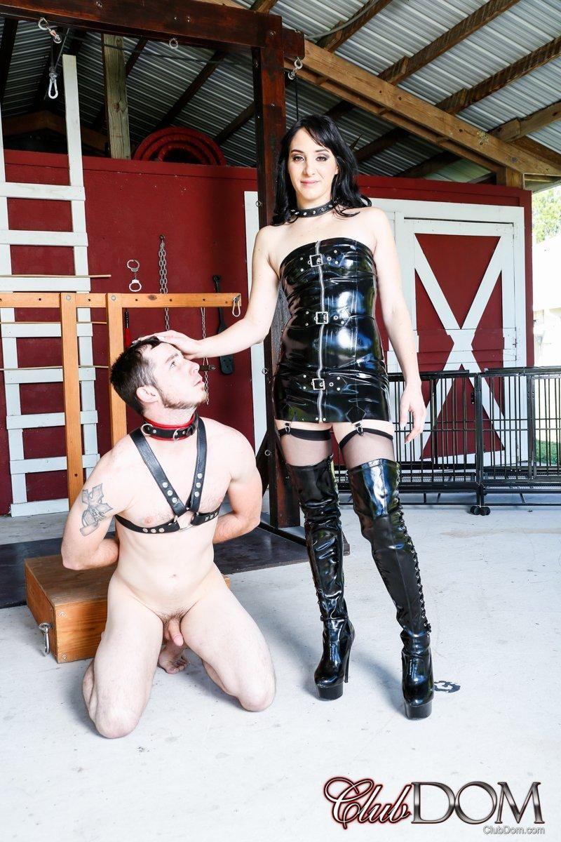 Sarah Dice from Club Dom dominates a male sub in a latex dress and boots