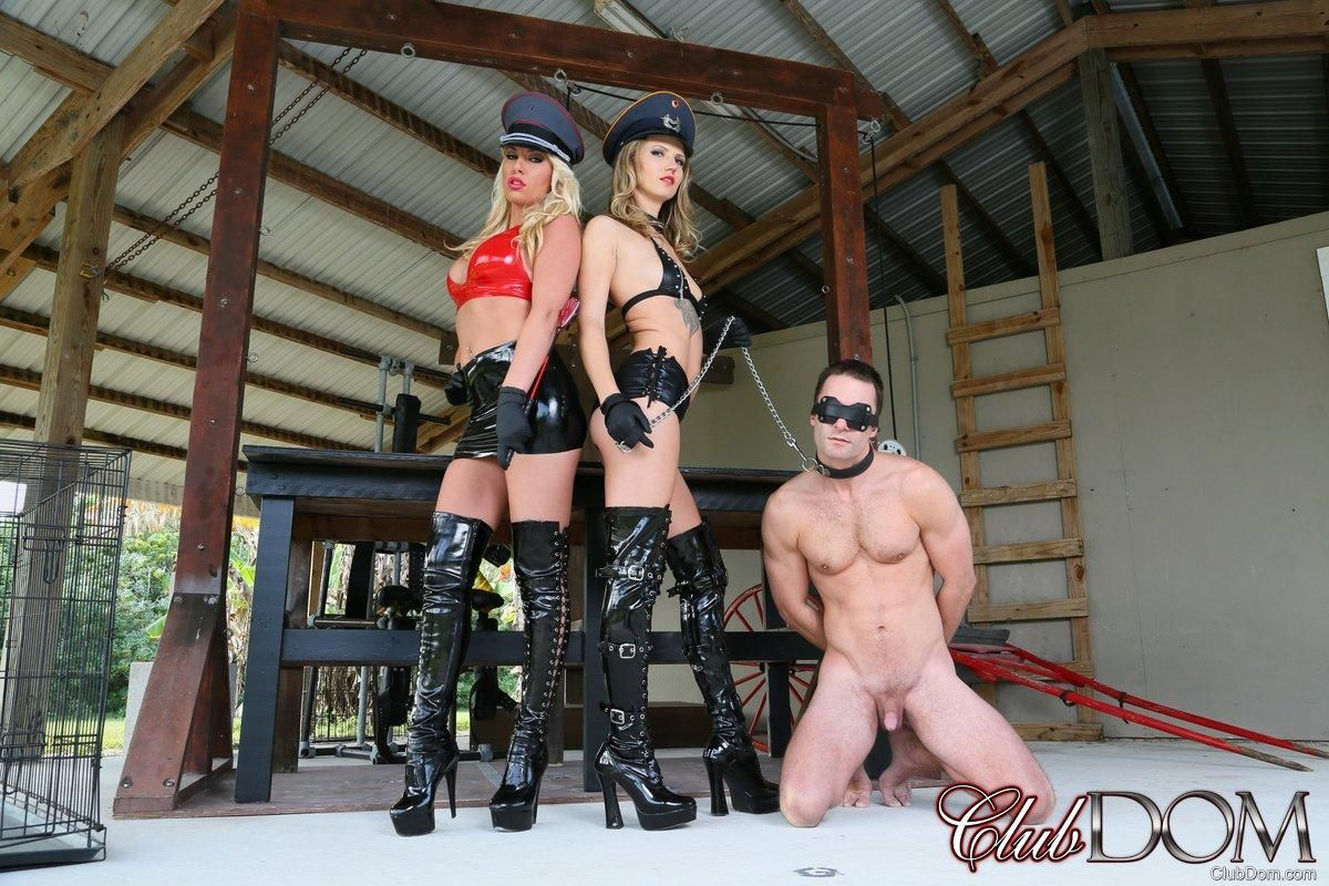 Beautiful blond Cherry Morgan and another wicked stunner trample a nude guy with long boots