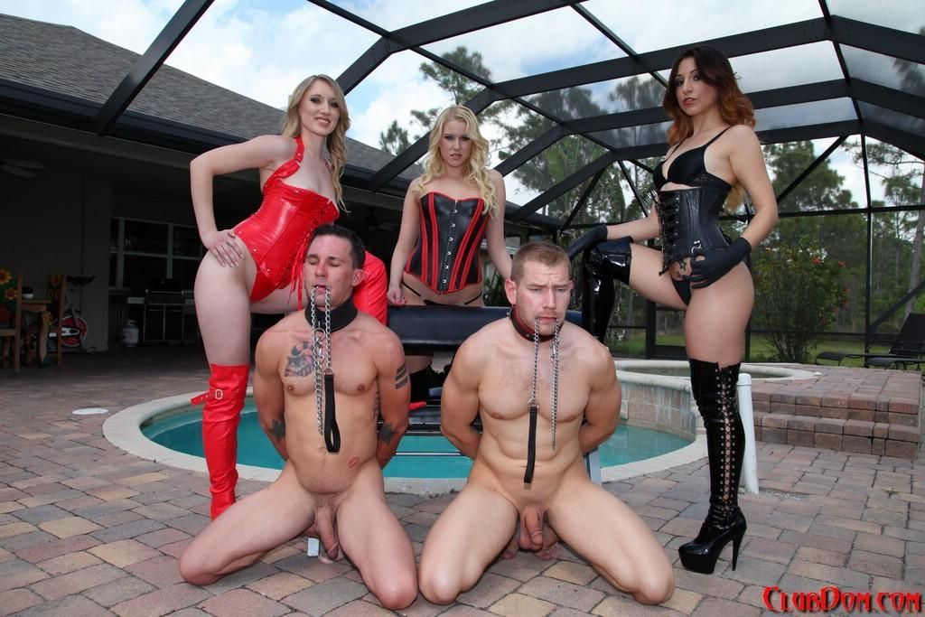 Sexy females in latex clothing and hip high boots manhandle collared male submissives by a pool