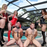 3 Dominas in fetish outfits manhandle 2 collared masculine submissives on the pool patio