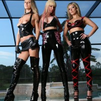 THREE tempting gals in latex garments and high heeled shoes debase masked masculine submissive by pool